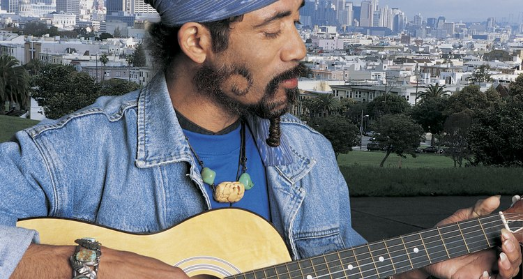 Mature Man With Funky Beard Playing Acoustic Guitar Against San Francisco Cityscape