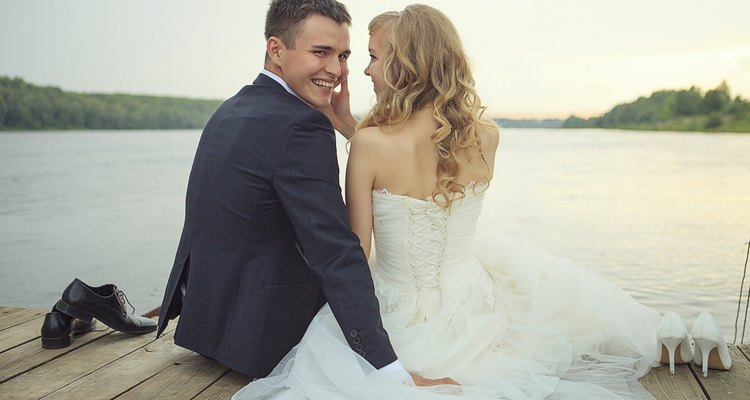 Bride with the groom sitting on a pier