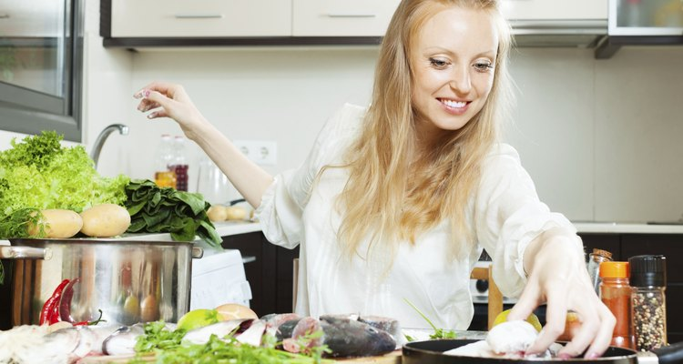 Happy woman putting  fish in flour into frying pan