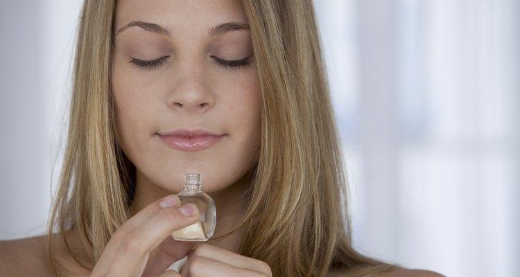 Woman smelling perfume.