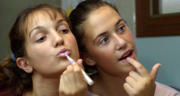 Teenage girls applying lip-gloss