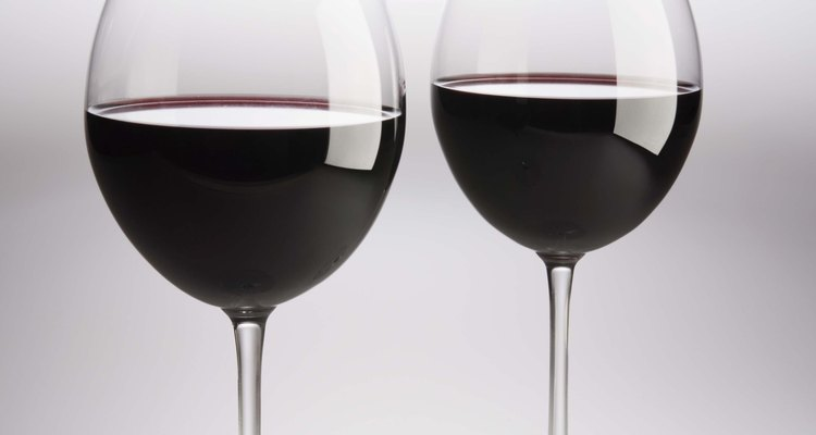 El vino rojo salpicado en una pared blanca manchará si se deja sin limpiar.