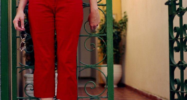 Woman in red capri pants standing by gated doorway