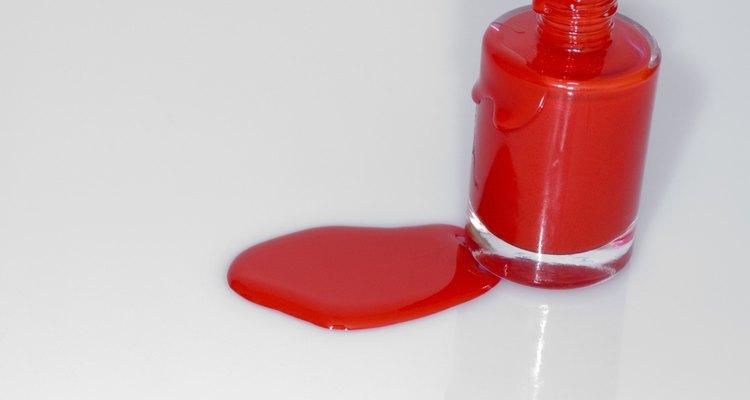 Elimina el esmalte de uñas rojo derramado en la ropa de lana usando quitaesmalte.