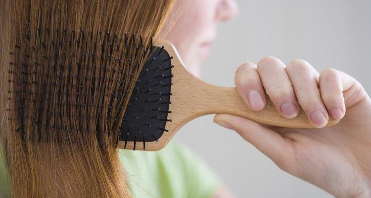 Trata tu cepillo con laca para el cabello o con una hoja para secadora antes de cepillarte el pelo.