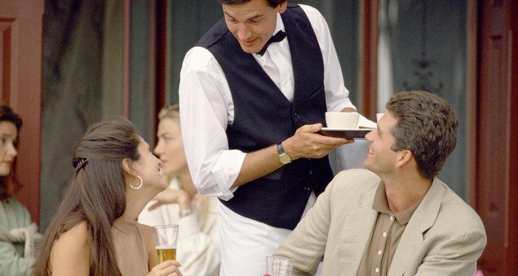 Los meseros llevan bebidas y alimentos a los clientes del restaurante.