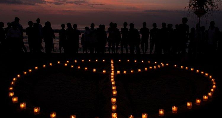 Pessoas ao redor de um símbolo feito com velas