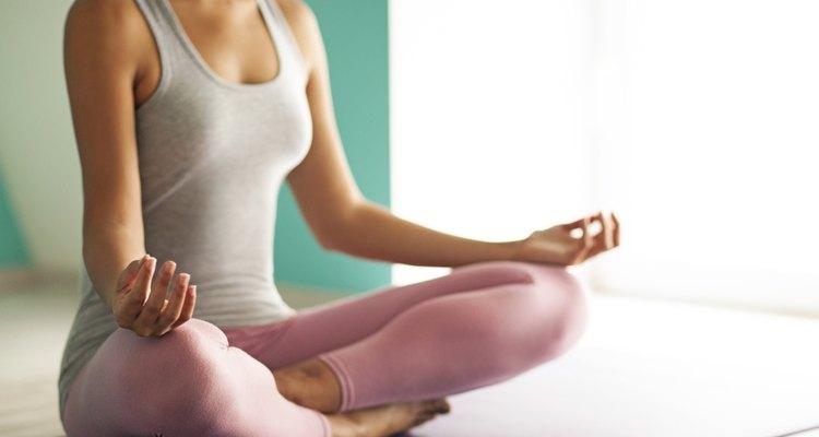 Una mujer medita en una alfombra de yoga.