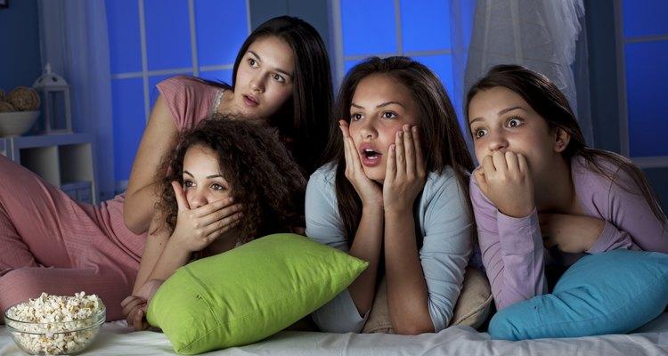 Adolescentes viendo una película con palomitas de maíz.