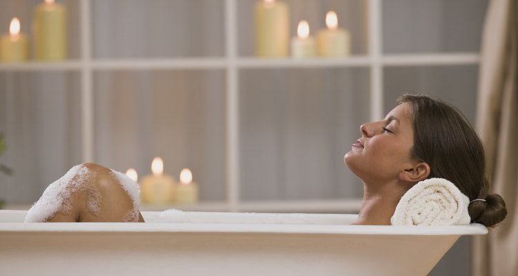 Content woman lying in bathtub with candles