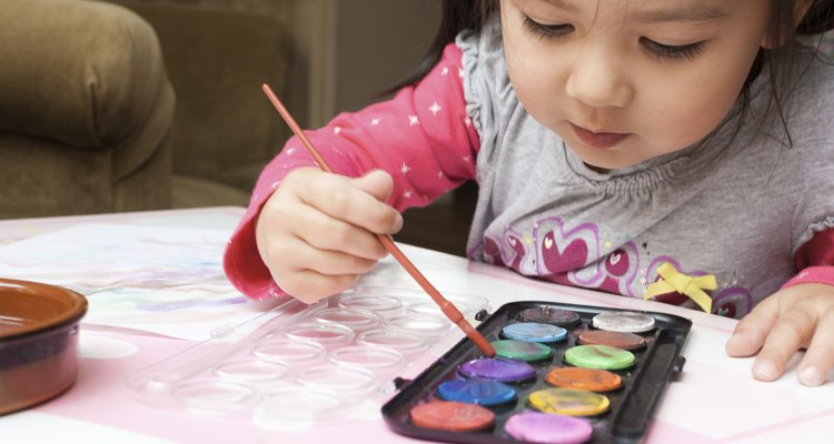 Little Asian girl learning to paint