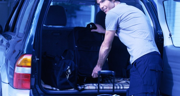 tungsten shot of a young man offloading luggage from the back of car