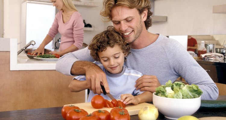 Father and son slicing vegetables