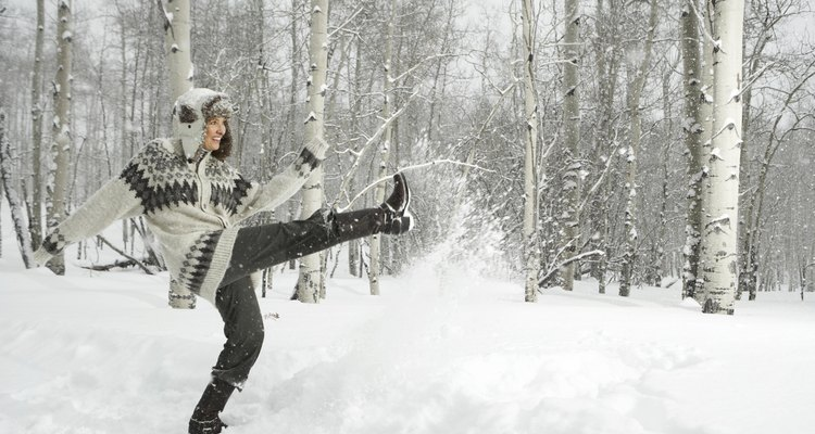 Mature woman playing in snow, smiling
