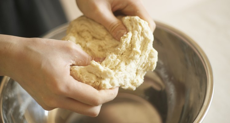 Woman making bagels, kneading dough, close up