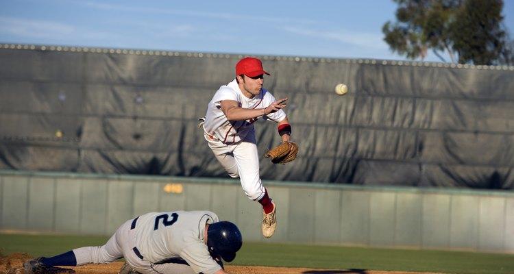 USA, California, San Bernardino, baseball runner sliding for base and baseman leaping for catch