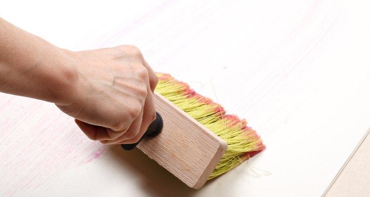 Hombre aplicando pegamento de papel tapiz.