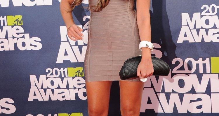 Amanda Bynes lleva zapatos de tacones color verde azulado con un vestido marrón en los MTV Movie Awards.