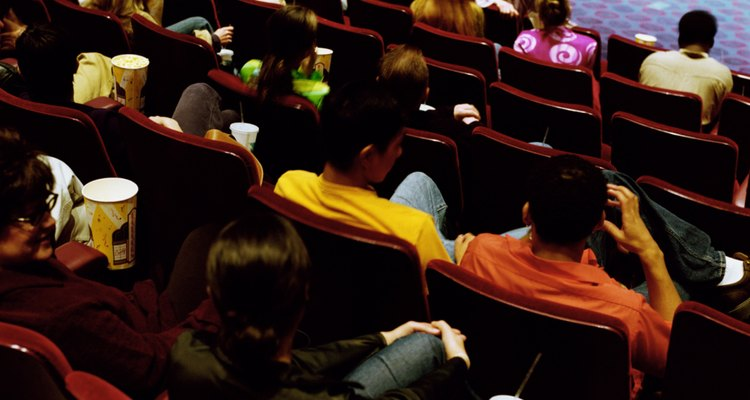 People sitting in movie theater, rear view