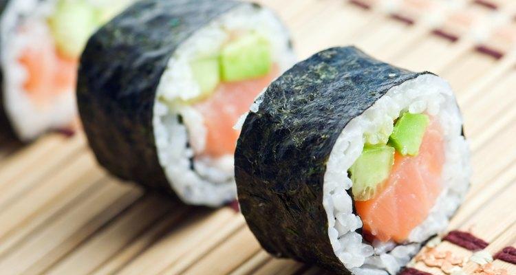 Três fatias de sushi enroladas em uma folha de bambu