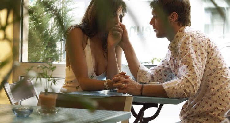 Couple at cafe table, woman kissing man's hand