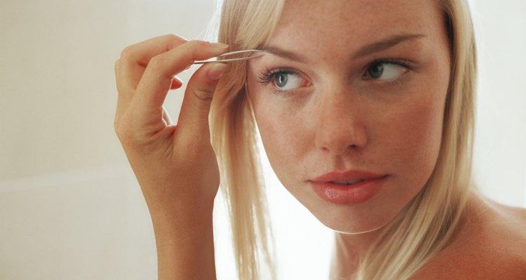 Woman plucking her eyebrow