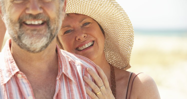 Mature couple laughing, portrait (focus on woman wearing straw hat)