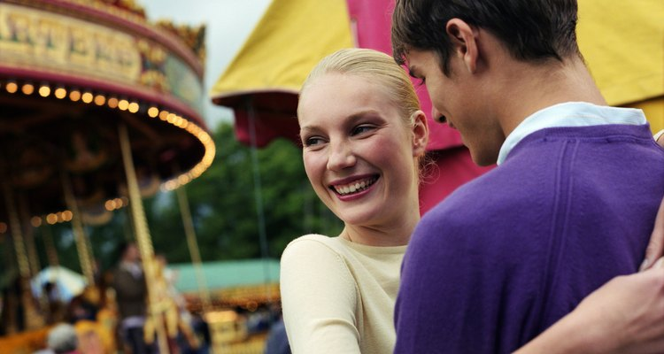 Young couple embracing at fairground, smiling, close-up