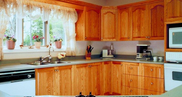 Los armarios de cocina de roble quedan bien con mesadas de granito blancas o grises.