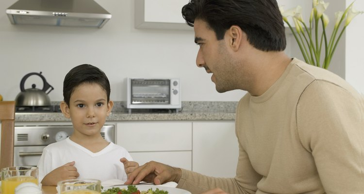 Man and boy sitting at table in kitchen, with salad and orange juice on table and man talking to boy, close-up