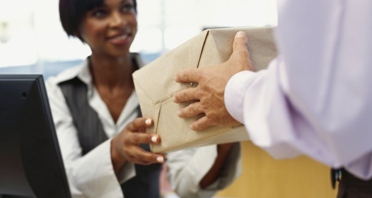 businesswoman receiving a package from a delivery man in an office
