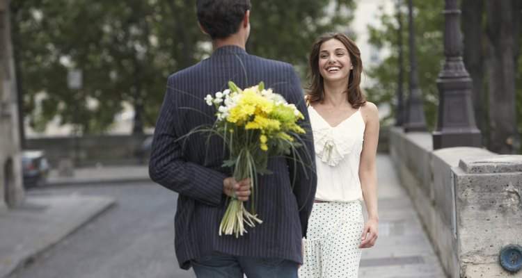 France, Paris, young couple outdoors, man holding flowers behind back