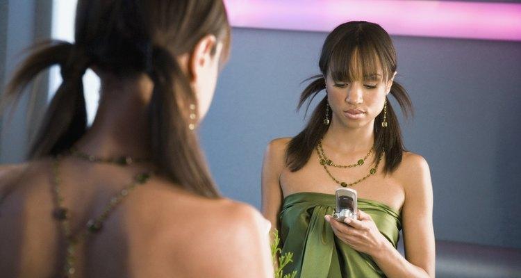 Uma jovem lê uma mensagem de texto em seu celular
