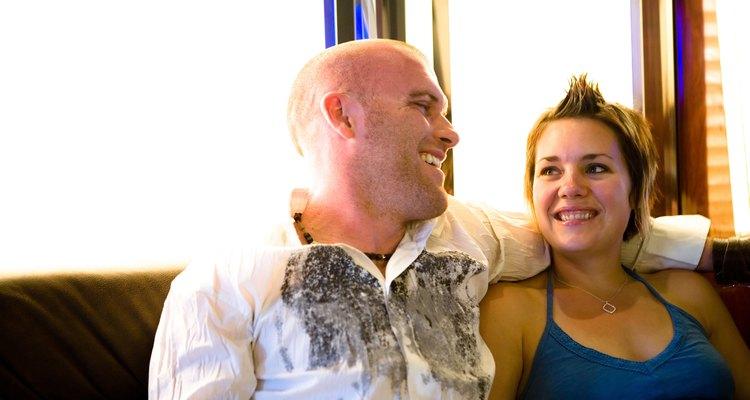 Hombre volteado hacia una mujer en un sofá, abrazándola.