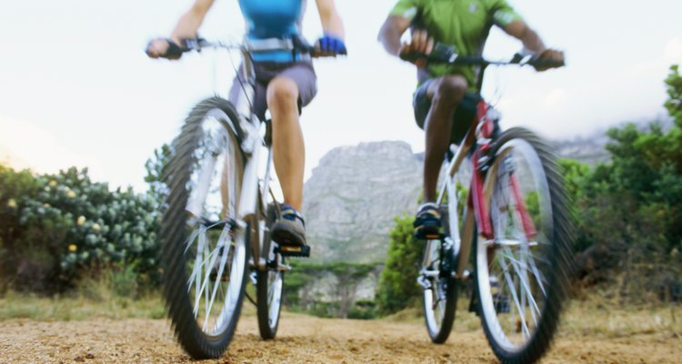 Low angle view of a young man and a young woman mountain biking