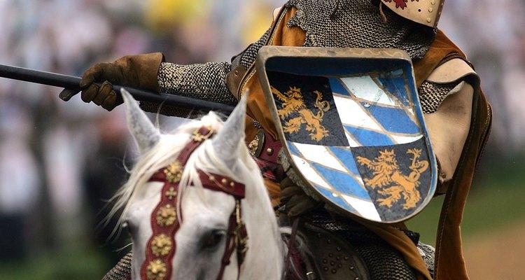 Um ator retratando um cavaleiro em uma justa carrega um pequeno escudo