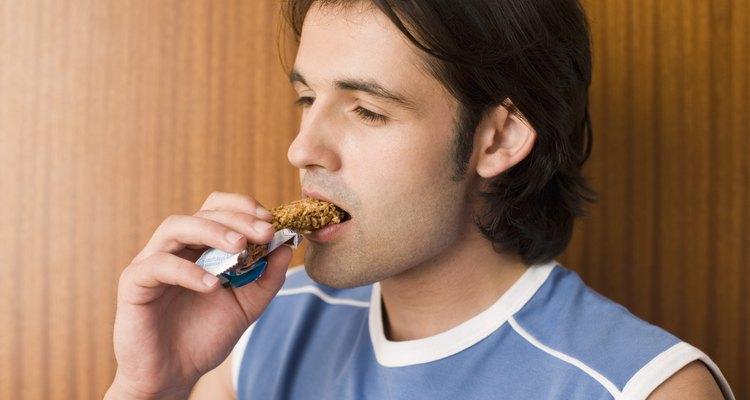 Homem comendo uma barra de granola