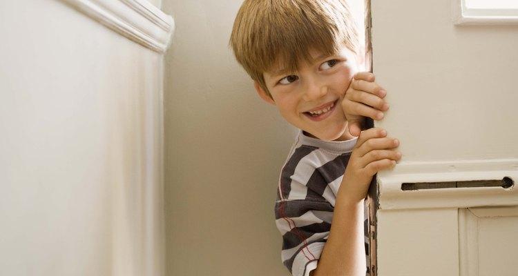 Boy peering around door