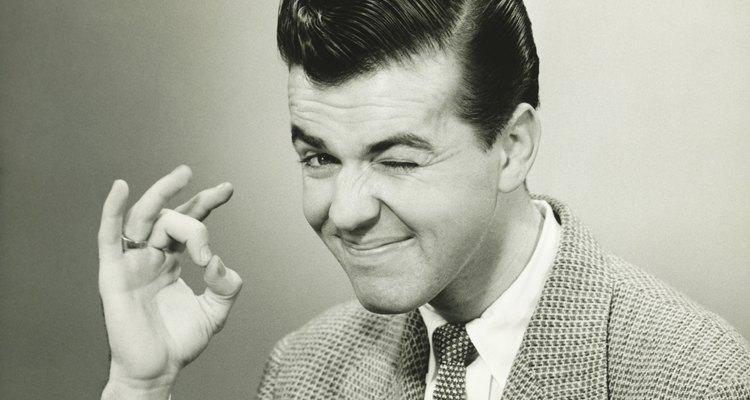 Man making OK gesture, winking in studio, (B&W), portrait