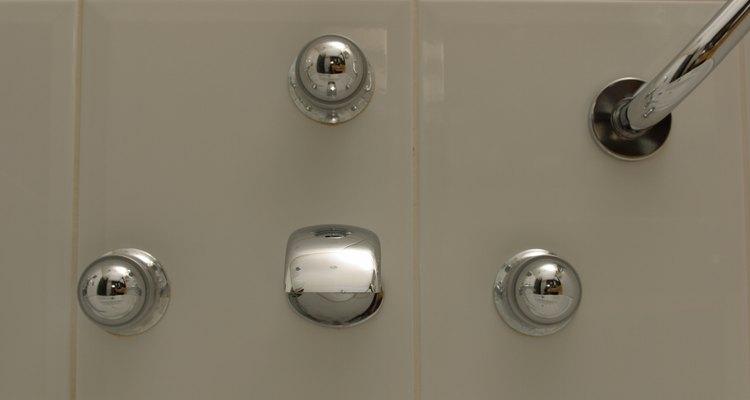 Limpia las zonas donde vive el moho en tu ducha con un limpiador especialmente hecho para ello y que sea a base de blanqueador.