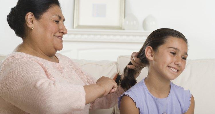 Hispanic grandmother brushing granddaughter's hair