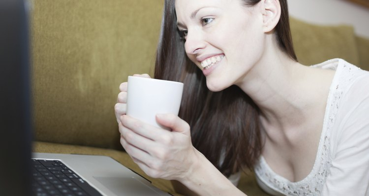 A woman holding a hot cup of tea while smiling at her computer screen.