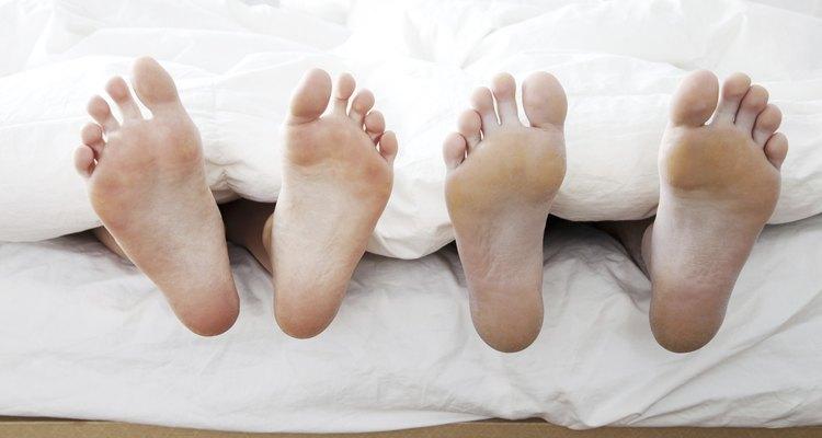 Dois pares de pés em uma cama
