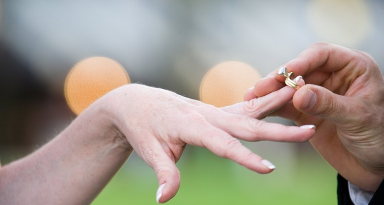 Man placing wedding ring on woman's finger outdoors