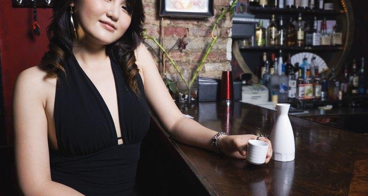 Smiling woman with sake at bar