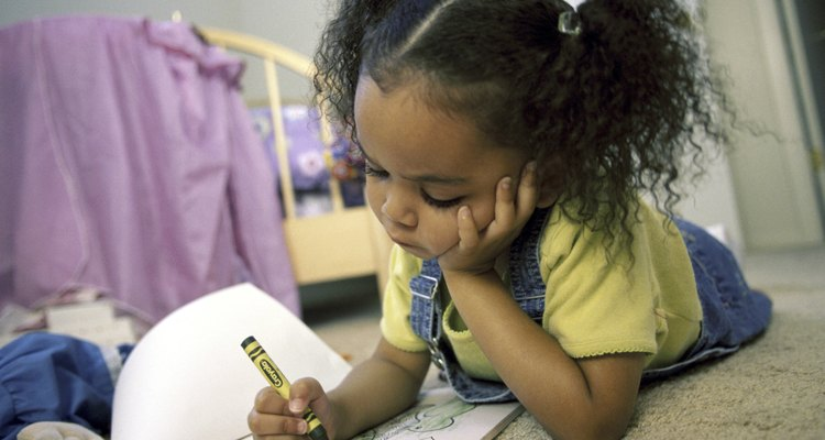 Girl coloring with crayons in a coloring book