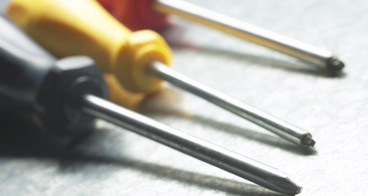 Quita los tornillos de la cuchilla que la sostienen en su lugar al frente de tu rasuradora con un destornillador.