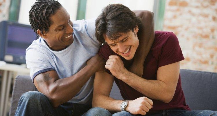 Multi-ethnic men hugging on sofa