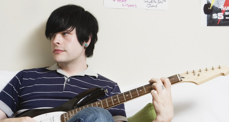 Man sitting on bed playing electric guitar