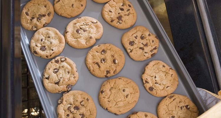 Woman removing cookies from oven
